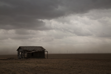 Picture of old shed in a field on a cloudy day.